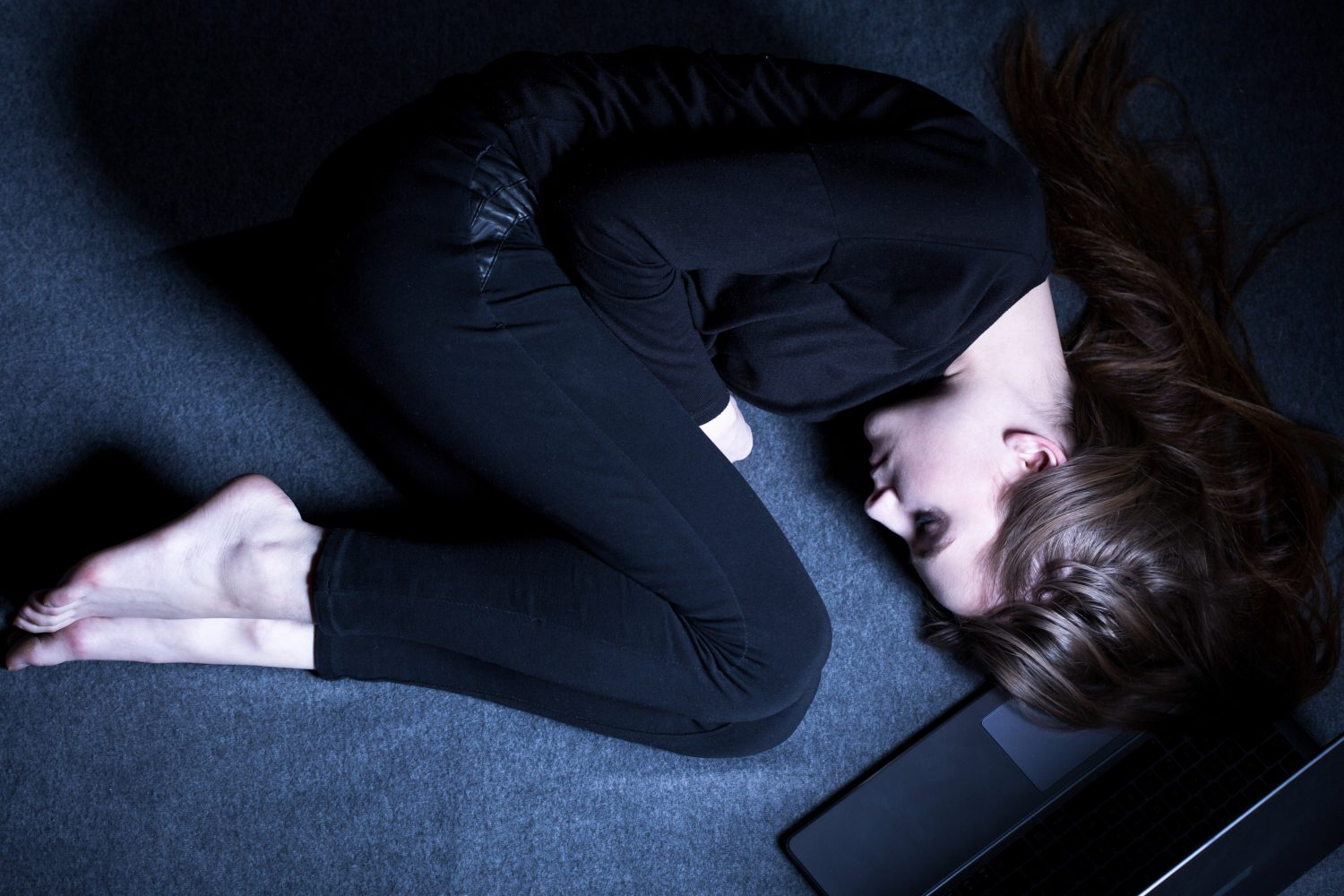 Women curled up on the floor thinking about addiction and Drug Detox