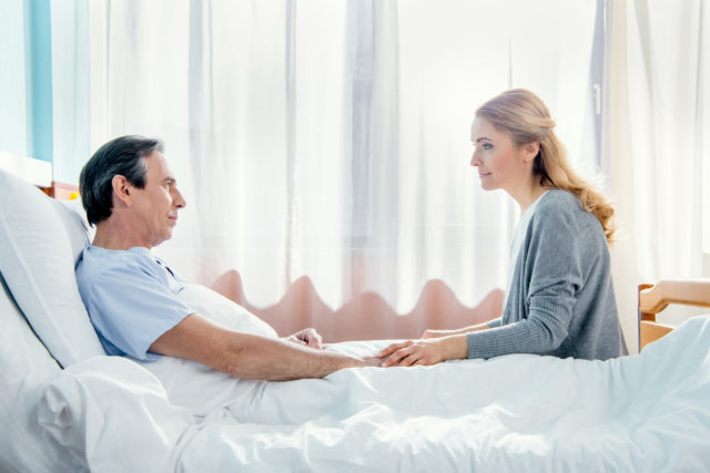 wife sits on hospital bed next to husband getting rapid detox for opioid dependence